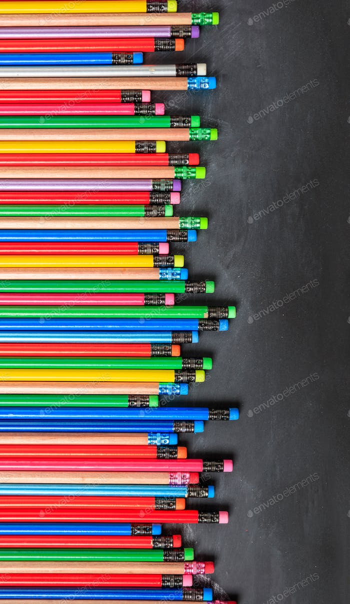 Colorful pencils with erasers on black board