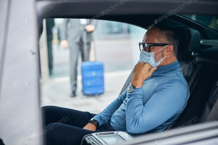 Pensive male passenger waiting for his driver