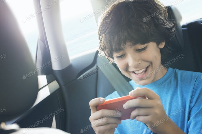 A boy sitting in a car using a handheld games tablet.