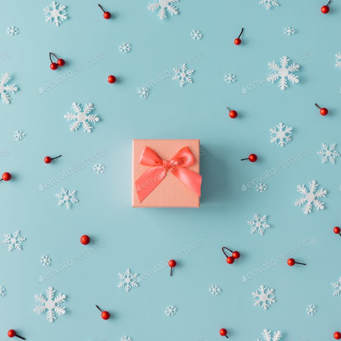 Christmas pattern made of snowflakes, red berries and gift box. Winter concept. Flat lay.