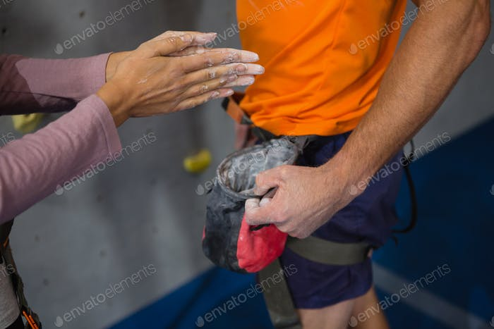Cropped hand of woman taking chalk powder from trainer
