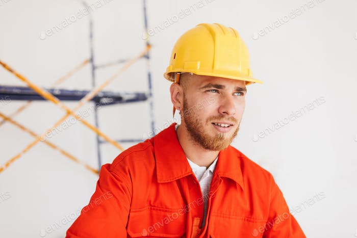 Portrait of young foreman in orange work clothes and yellow hard