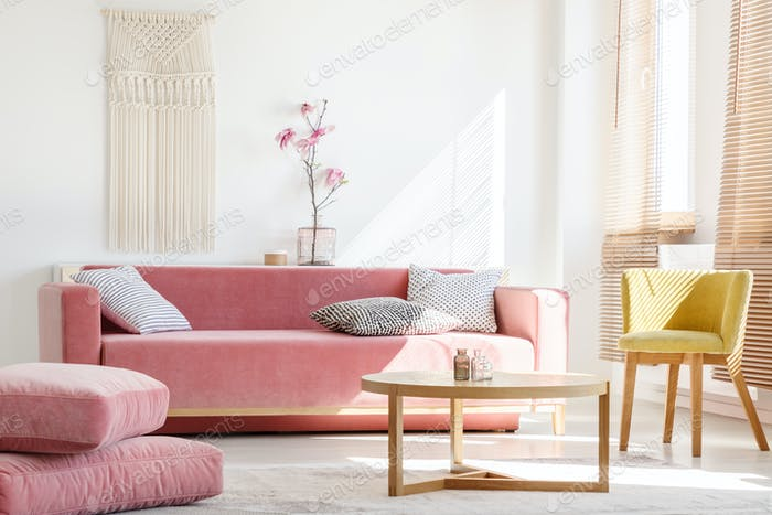 Real photo of a pink couch with pillows standing next to big pil