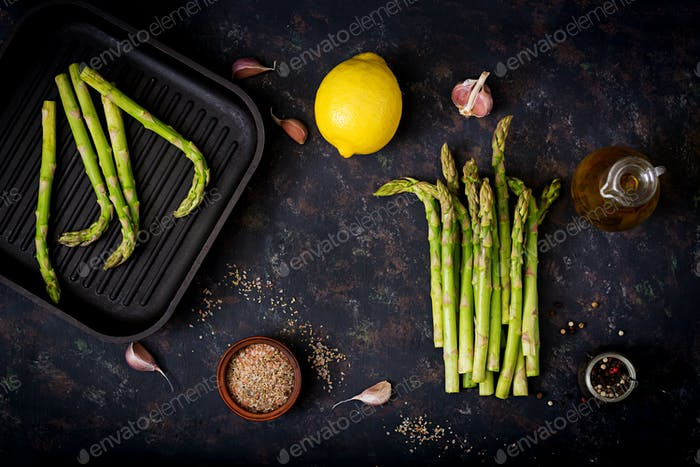 Fresh asparagus and ingredients for cooking on dark background. Flat lay. Top view