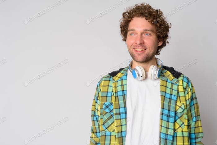 Happy handsome hipster man with curly hair thinking