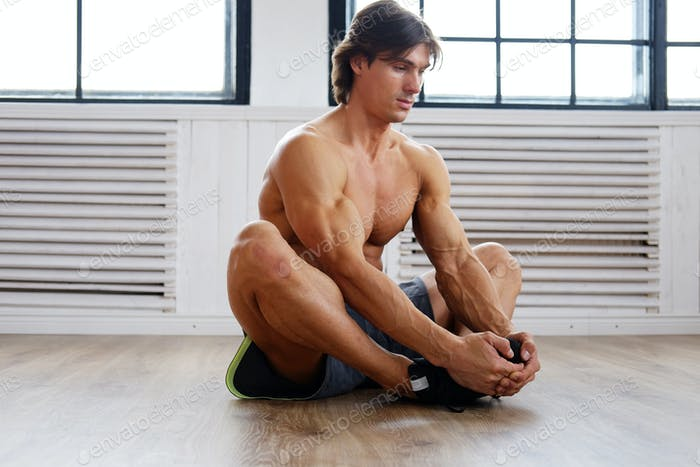 SHirtless sporty male on a floor.