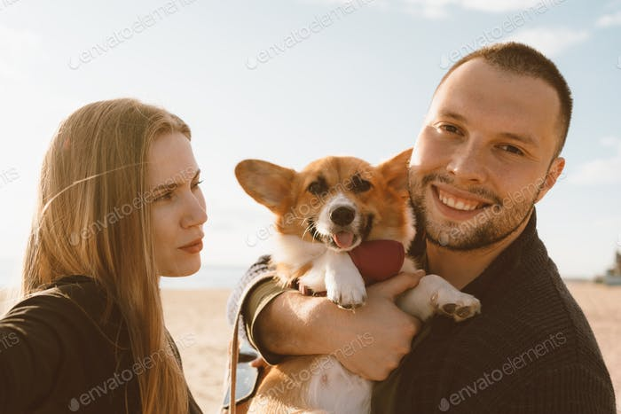 Young happy couple with dog taking selfie on beach. Beautiful woman and man and Corgi
