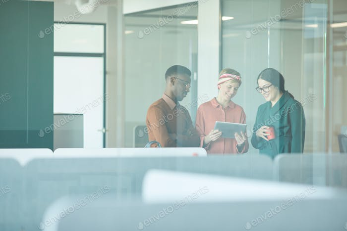 Ethnic Team Behind Glass in Modern Office
