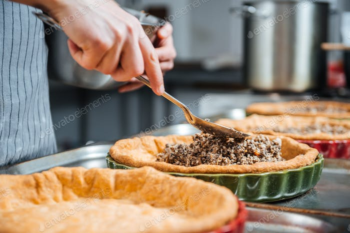 Hands of cheif cook cooking and putting filling into pie