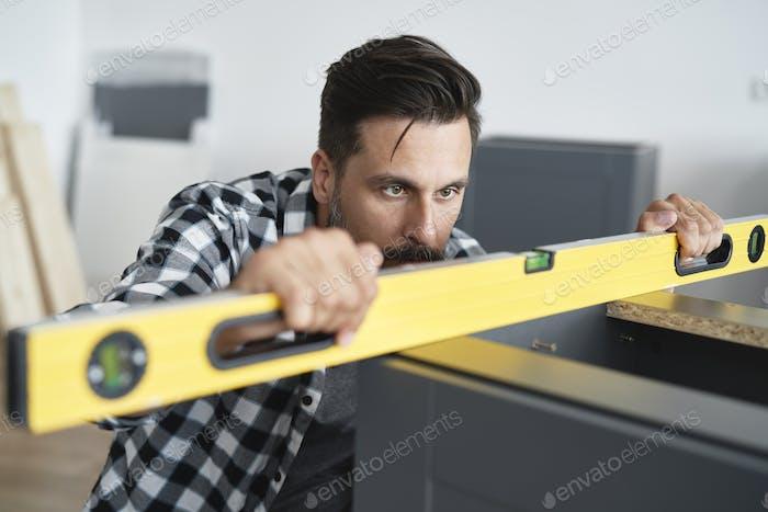 Mann Überprüfung der Möbel Ebenen mit einer Wasserwaage