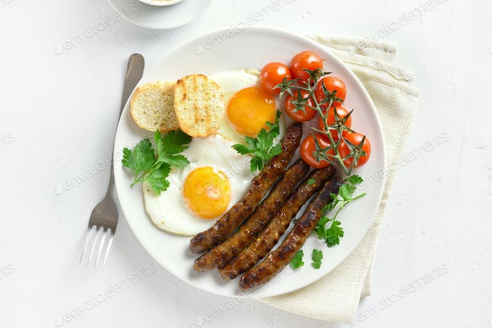 Fried eggs, sausages and cherry tomatoes