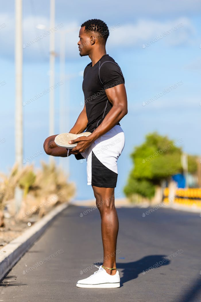 Black african american young man stretching after outdoor joggin