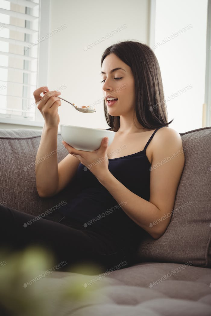 Smiling woman eating breakfast while sitting on sofa