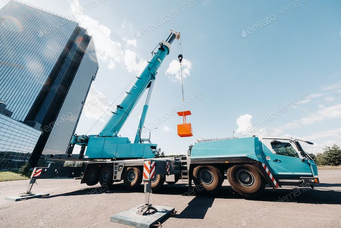 A large blue truck crane stands ready for operation on a site near a large modern building. The