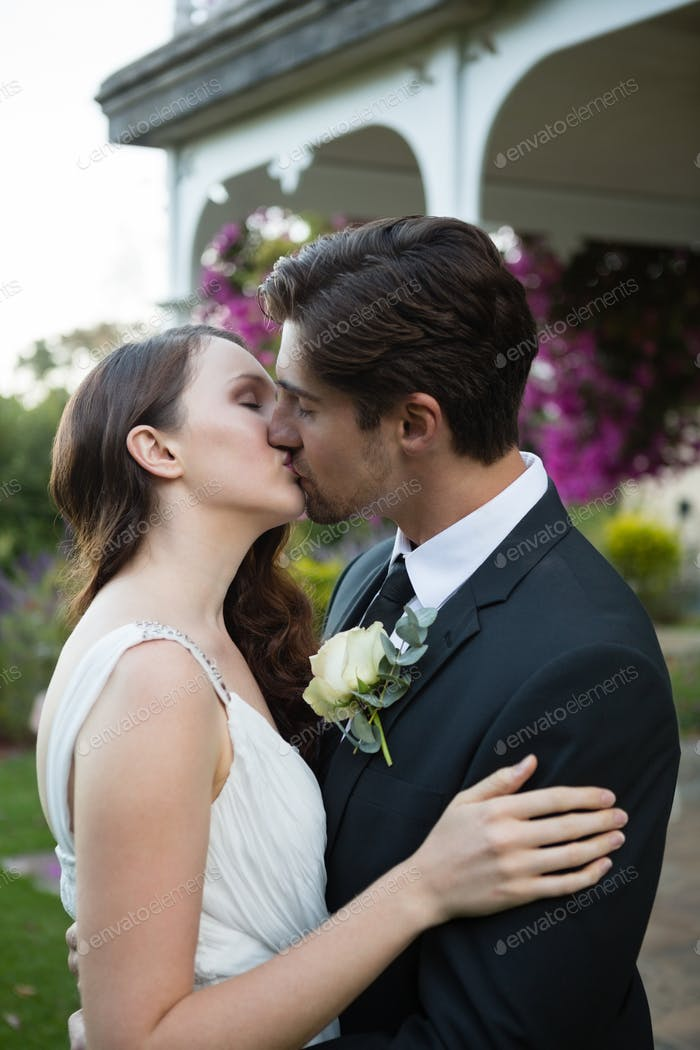 Romantic couple kissing while standing in park