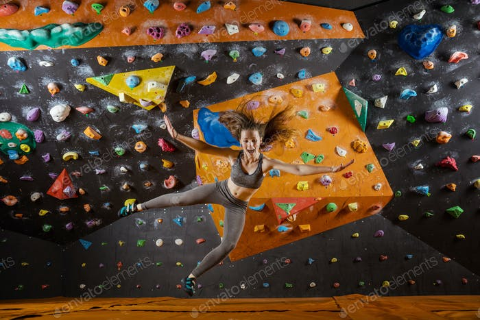 Young woman falling down while bouldering in indoor climbing gym