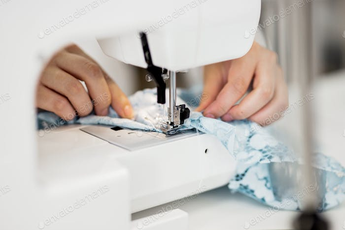 A woman is sewing with the electric sewing-machine. Fashion, tailor's workshop