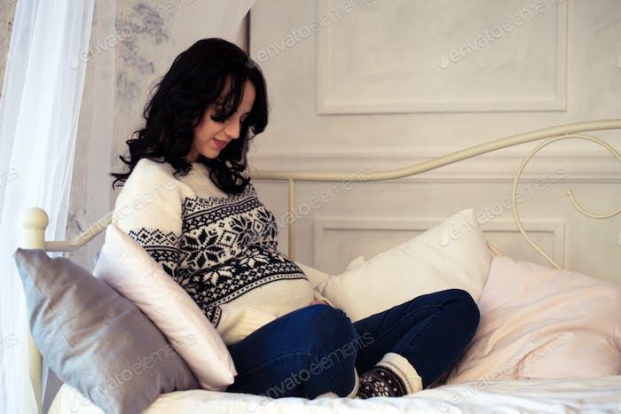 Schwangere Frau ruht auf dem Sofa im Zimmer