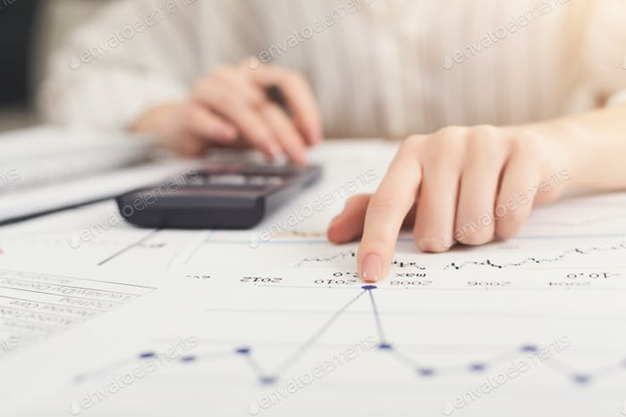 Closeup of woman hands working with documents and calculator