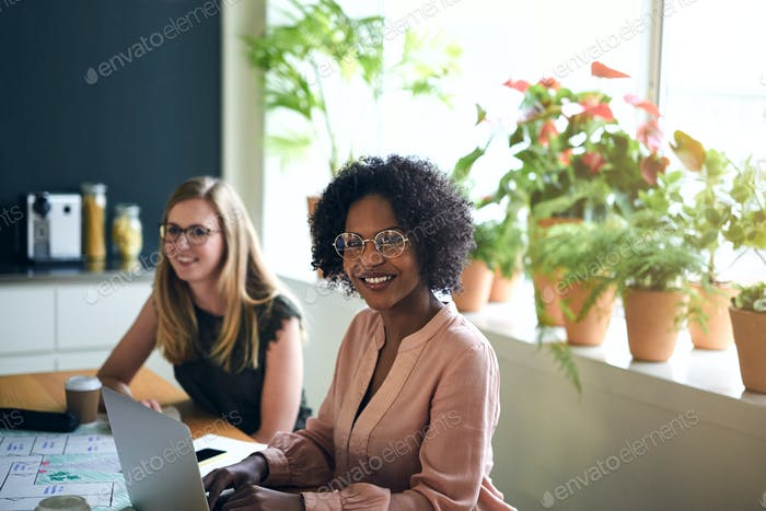 Confident African businesswoman working with a colleague in an office