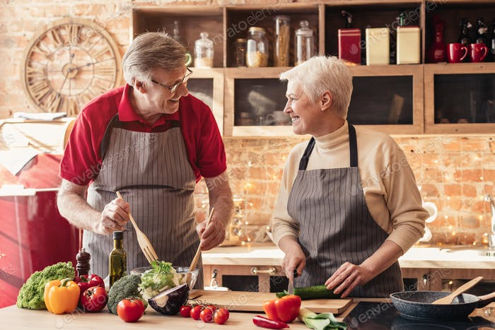 Cheerful senior couple cooking healthy lunch together at kitchen