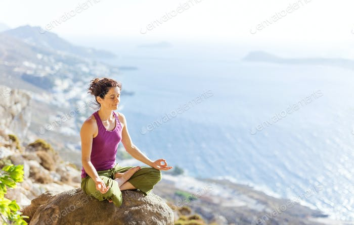 Caucasian young woman practicing yoga while sitting in lotus pose