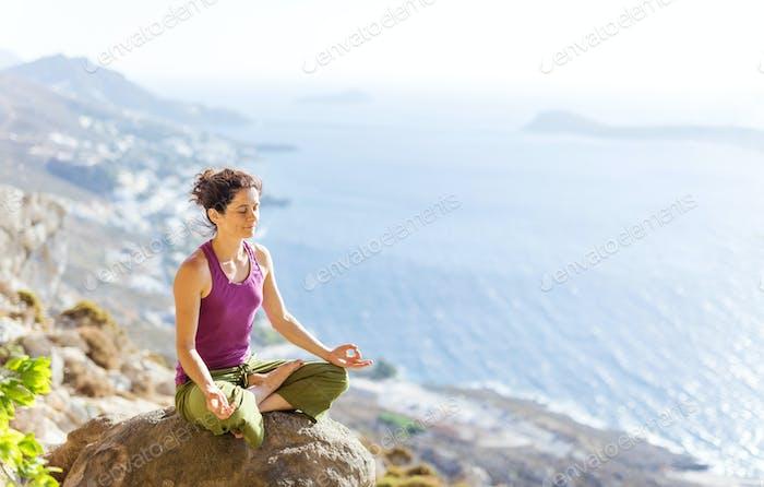 Mujer joven caucásica practicando yoga mientras se sienta en pose de loto