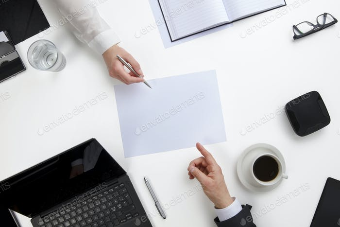 Business People Discussing Over Document At White Desk