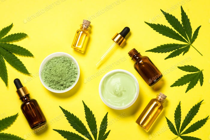 Cannabis oil and green leaves at yellow table