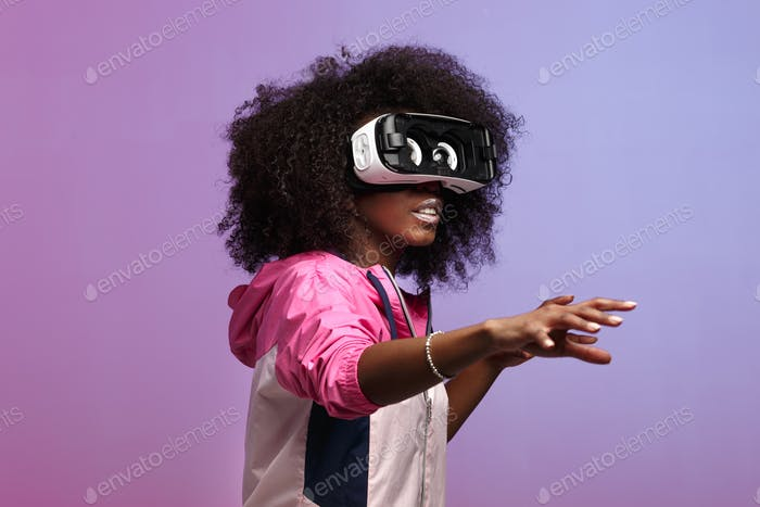 Mod junge braunhaarige lockige Mädchen in der rosa Sportjacke gekleidet verwendet die Virtual Reality Brille