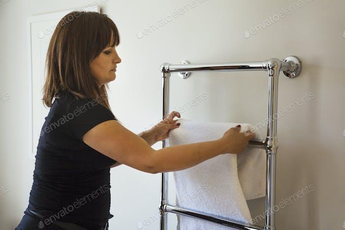 Woman standing in a bathroom, hanging fresh towel over metal towel holder.
