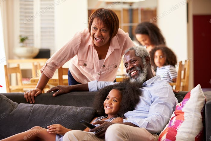 Grandparents With Granddaughter Sitting On Sofa At Home Watching Movie With Family In Background