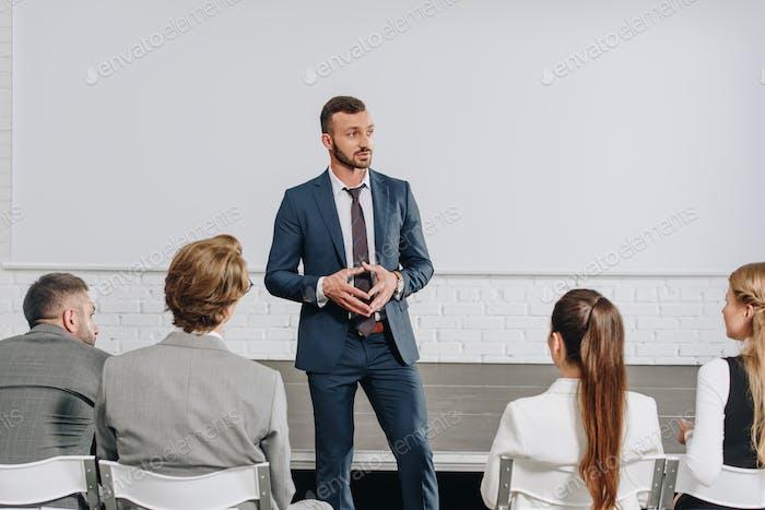 pensive business trainer looking away in hub