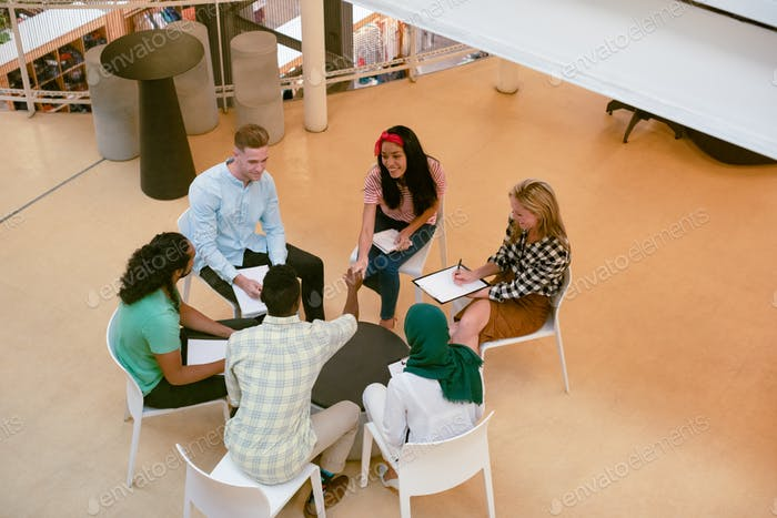 High angle view of diverse business people discussing with each other in a modern office