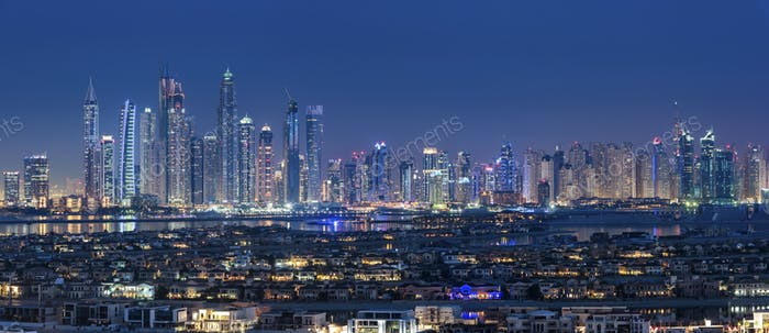 Cityscape of Dubai, United Arab Emirates at dusk, with illuminated skyscrapers in the distance.