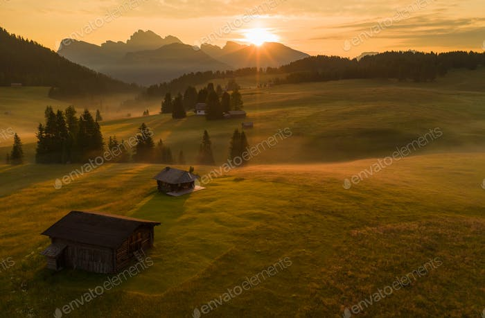 Mountain meadows of the Dolomites in the morning fog