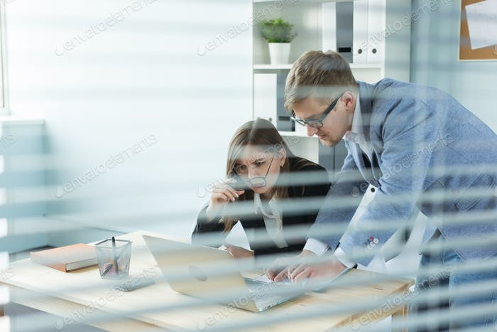 Business, teamwork and people concept - woman and man are working together in office