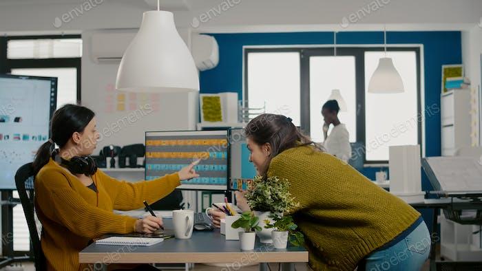 Diseñadores gráficos que analizan los activos del cliente desde pantallas comprobando el engreading de color