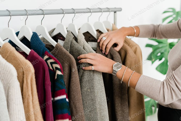 Casual young female shopaholic choosing jacket or sweater in boutique