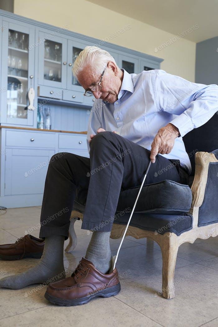 Senior Mann in Stuhl mit Hilfe zu setzen auf Schuh