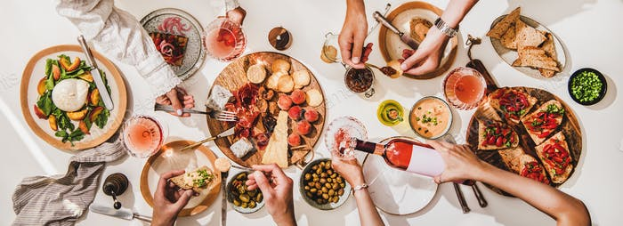 Wine and snacks party with rose wine, salads and appetizers