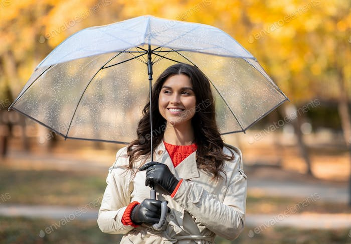 Portrait of cheerful young woman walking under autumn rain at yellow park