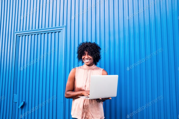 one beautiful african or american black woman smiling and using laptop or computer pc enjoying