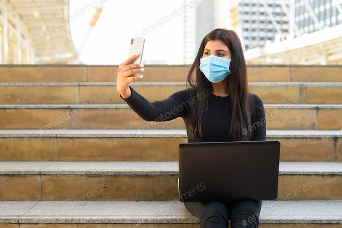 Young Indian woman with mask using laptop and video calling with phone by the stairs in city