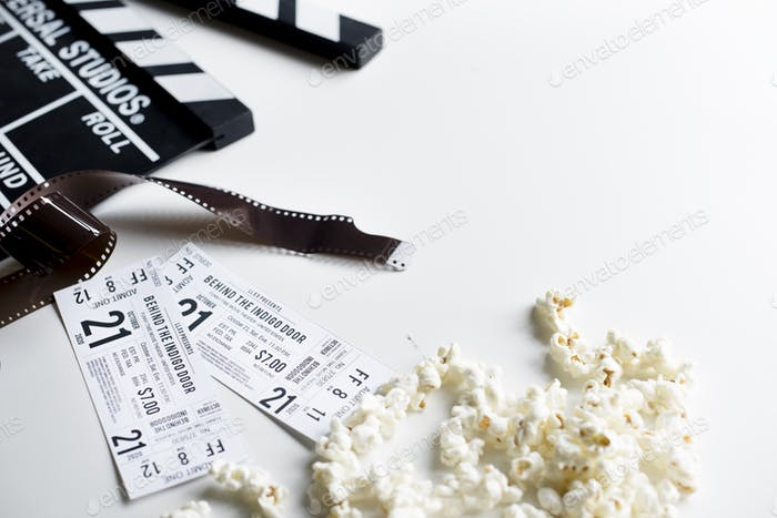 Closeup of movie tickets with popcorn and reels decoration on wh