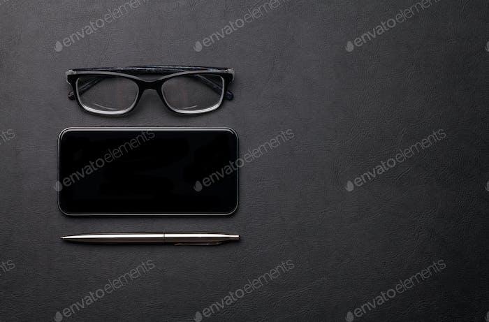 Bürotisch mit Smartphone, Brille und Zubehör
