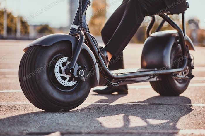 Человек ездит на своем новом электро скутере
