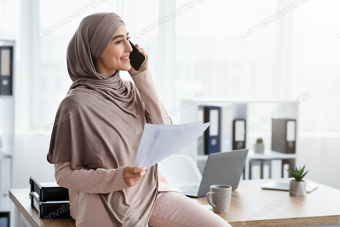Millennial muslim businesswoman holding papers and talking on cellphone in office