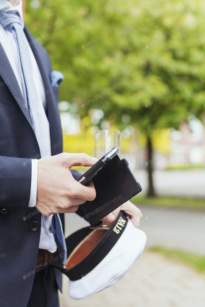 Midsection of male graduate using smart phone at campus