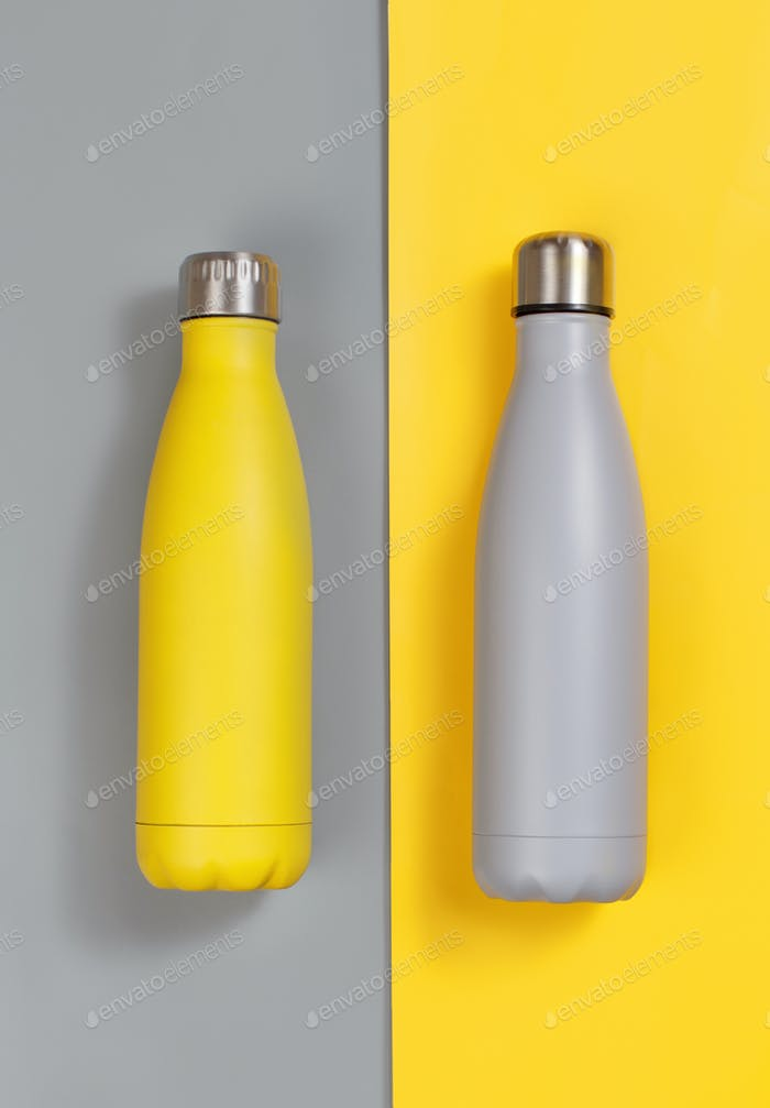Grey and yellow insulated reusable bottles on grey and yellow background